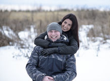 Young couple outdoors playing, cuddling in winter park. Girl hugging her boyfriend. Happy relaxing families Stock Image