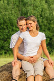 Young couple outdoors sit on hay Royalty Free Stock Photos