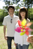 Young couple outdoors, woman holding out pinwheel, portrait (blurred motion) Royalty Free Stock Images