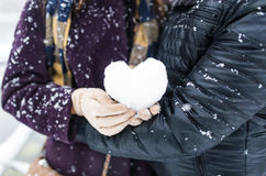 Young couple outside with a heart shape snowball Stock Image