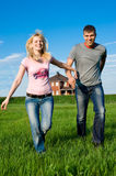 Young couple outside their home. Happy couple running outdoors outside their home Stock Images