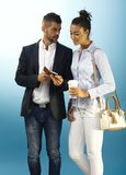 Young couple over blue background. Young couple looking at mobilephone over blue background Royalty Free Stock Photo