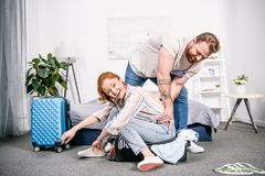young couple packing clothes for trip while woman royalty free stock images