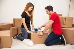 Young couple packing some boxes. Cute young couple packing some of their stuff to move to their new home stock photos