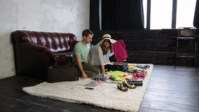 Young couple packing stuff into suitcase at home stock video footage