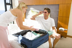 Young couple packing suitcase on bed, man wearing sunglasses, smiling at woman royalty free stock photo
