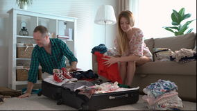 Young couple packing suitcase on floor in room stock video