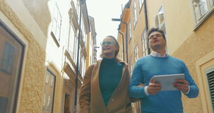 Young couple with pad walking in old narrow street. Steadicam shot of young happy man and woman with pad having a walk along the old narrow street in Stockholm stock footage