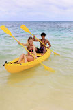 A young couple paddle a kayak in Hawaii Stock Photography