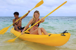 A young couple paddle a kayak in Hawaii Royalty Free Stock Photo