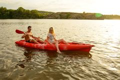Free Young Couple Paddling Kayak On Beautiful River Or Lake In The Evening At Sunset Stock Image - 116676781