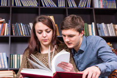 Young couple paging through a book in the library Royalty Free Stock Photography