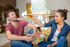 Young couple with paintbrushes and palette having fun while sitting on floor Stock Photo