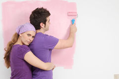Young couple painting baby nursery in new home Royalty Free Stock Images