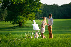 Young couple painting. On an easel in a field Royalty Free Stock Image