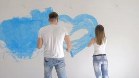 Young couple painting heart on wall with blue paint stock footage
