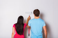 Young couple painting with roller Stock Photo
