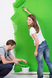 Young couple painting their new home green. Working as a team as the husband does the skirting boards and the happy young wife smiles at the camera as she uses Royalty Free Stock Photo