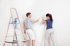 Young couple painting wall at home Stock Photos