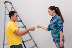 The young couple painting wall at home Royalty Free Stock Photo