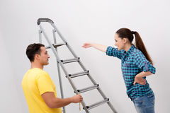 The young couple painting wall at home Stock Images