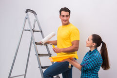 The young couple painting wall at home Stock Image