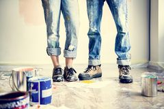 Young couple painting a wall home renovation concept stock images