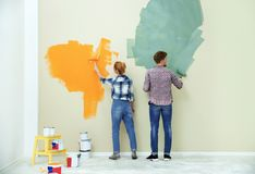 Young couple painting wall. Home repair stock photo