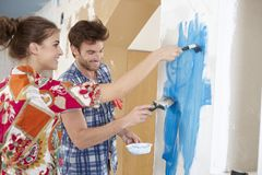 Young couple painting wall to blue Stock Image