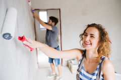 Young couple painting walls in their new house. Stock Images