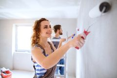 Young couple painting walls in their new house. Beautiful young couple having fun and painting walls using paint rollers in their new house. Home makeover and Royalty Free Stock Photo