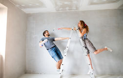 Young couple painting walls in their new house. Beautiful young couple at home standing on ladder painting walls in their new house using paint rollers. Home Royalty Free Stock Images