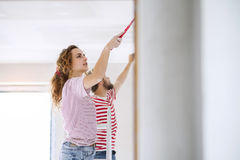 Young couple painting walls in their new house. Stock Photos