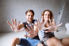 Young couple painting walls in their new house. stock image