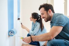 Renovation diy paint couple in new home painting wall together. Young couple painting walls in their new house, do it yourself concept royalty free stock image