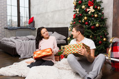 Young couple in pajamas rejoice at their presents while sitting Royalty Free Stock Photo