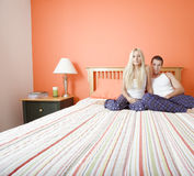 Young Couple in Pajamas Sitting on Bed Stock Photography