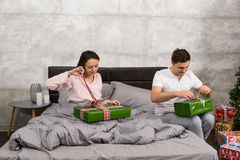Young couple in pajamas unpacking their presents while sitting o Stock Images