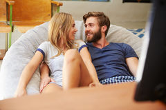 Young Couple In Pajamas Watching Television Together Stock Images