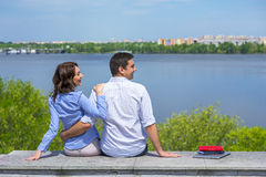 Young couple on parapet looking sideward Royalty Free Stock Photos