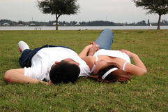 Young couple in park. A young couple lying in the grass holding hands Royalty Free Stock Photo