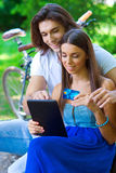 Young couple on the park bench with credit card and tablet Royalty Free Stock Image