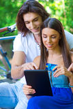 Young couple on the park bench with credit card and tablet Stock Photography