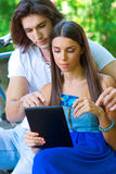 Young couple on the park bench with credit card and tablet Stock Photo