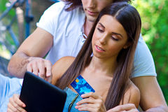 Young couple on the park bench with credit card and tablet Royalty Free Stock Photography