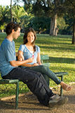 Young Couple on a Park Bench - Vertical Royalty Free Stock Photo