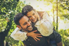Boyfriend carrying his girlfriend on piggyback. Spring season. Young couple in park. Boyfriend carrying his girlfriend on piggyback royalty free stock photography