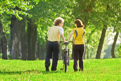 Young couple in the park with a bycicle Royalty Free Stock Photo