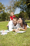 Young couple in park with child. A young caucasian couple in matching white outfits in the park with their young boy Royalty Free Stock Images