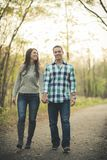 Couple holding hands smiling walking together in the park stock image